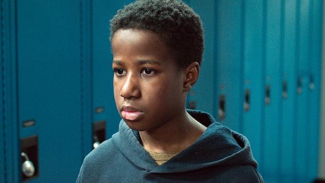 Un jeune garçon au regard sérieux, devant une rangée de casiers.