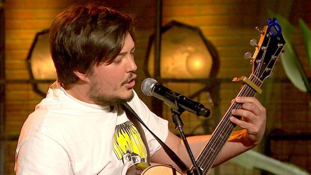 Émile Bilodeau chante en jouant de la guitare.