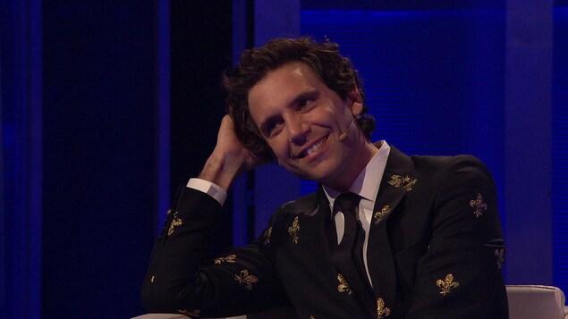 Mika regarde la prestation en souriant.