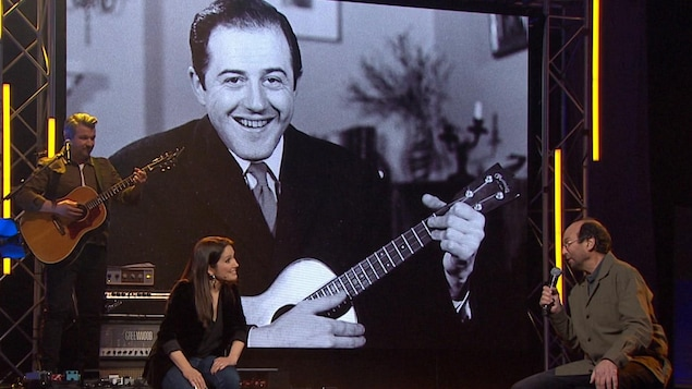 France Beaudoin et Michel Rivard discutent devant un écran avec une photo de Raymond Lévesque.