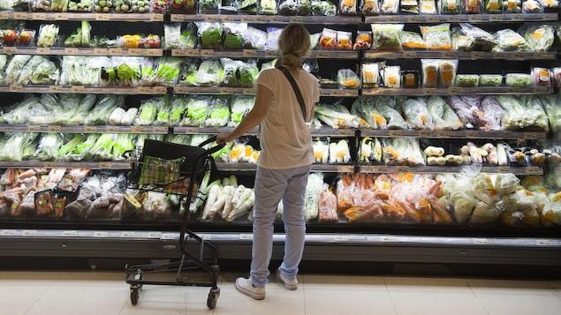 Des légumes emballés par des pellicules de plastique dans une épicerie.