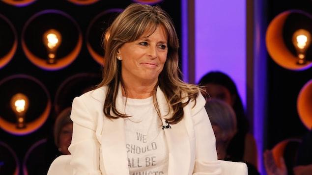 Fabienne porte un t-shirt blanc qui affiche le message « We should all be feminists » et un veston blanc.