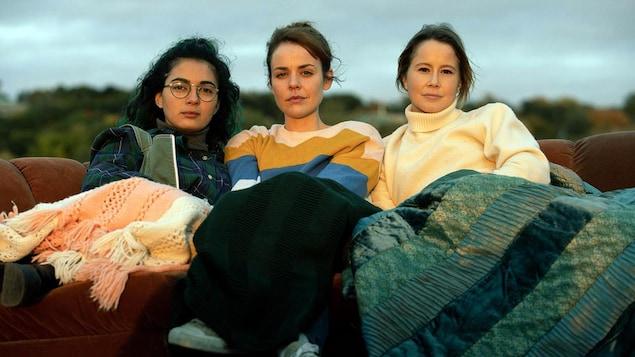 Trois jeunes filles assises sur un divan, à l'extérieur, des couvertures sur les jambes.