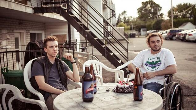 Deux jeunes hommes (dont Pier-Luc Funk et un autre en chaise roulante) assis autour d'une table, dehors, dans un parking.