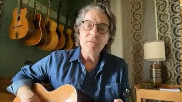 Il est en vidéoconférence, une guitare à la main, dans une pièce de sa maison.