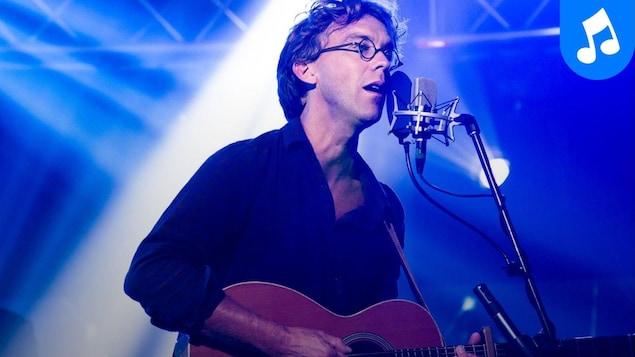 Le chanteur et conteur joue de la guitare en chantant sur le plateau d'En route vers le gala de l'ADISQ.
