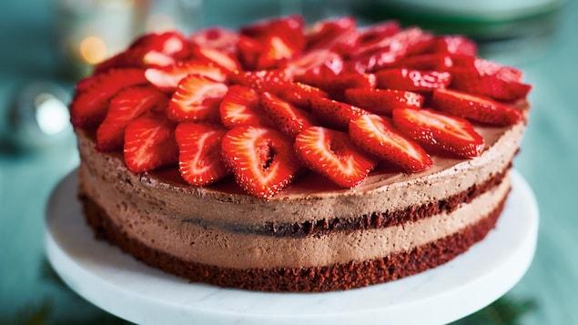 Un gâteau sur lequel on a déposé des tranches de fraises.