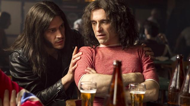 Un homme portant un manteau de cuir (Eric Bruneau) les mains sur les épaules d'un autre homme assis et portant un t-shirt rouge (Mario Saint-Amand), devant une table jonchée de bouteilles de bière.