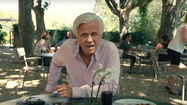 Un homme âgé (Alex Lutz) attablé dans un café à l'extérieur regarde la caméra.