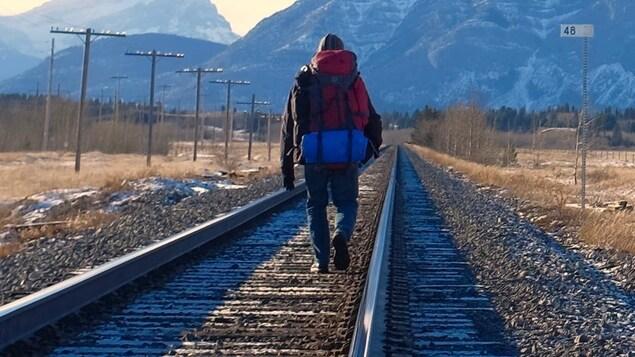 Il porte un sac à dos. Devant lui se dressent des montagnes.