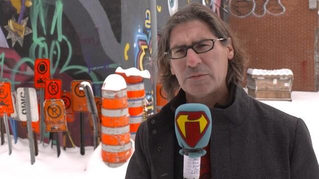 Un homme se tient devant un bâtiment. Derrière lui, il y a plusieurs affiches indiquant l'interdiction de stationner. Il y a de la neige au sol.
