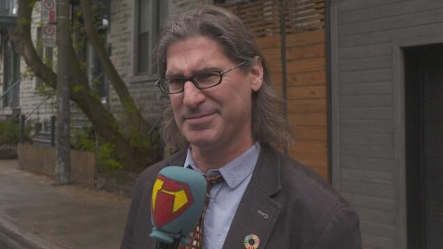 Jean-René Dufort qui sourit avec son micro à la main.