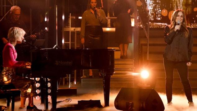 Les deux femmes chantent sur scène pour Roxane Bruneau.