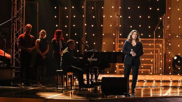 Elle est sur scène avec un pianiste et des choristes.