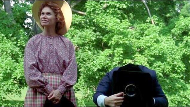 Une femme souriante, à côté d'un homme la tête sous le drap d'un appareil photo