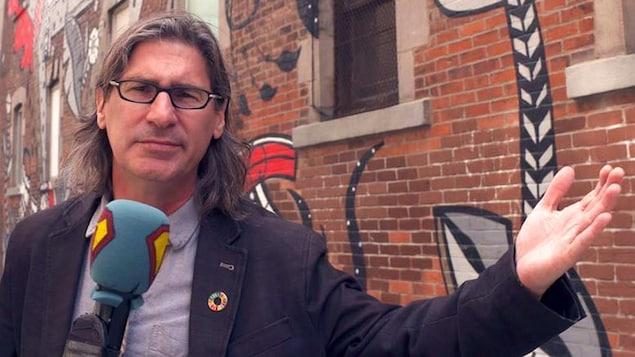 L'animateur est à l'extérieur devant un mur couvert de graffitis. Il tient son micro et lève un bras.