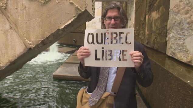 Un homme qui tient une petite affiche où l'on peut lire : Québec livre
