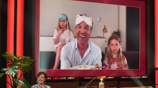 Un homme qui sourit. Il apparaît dans un écran avec ses deux filles.