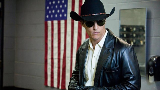 Un homme portant chapeau, lunettes et de veste de cuir noirs devant un drapeau américain.
