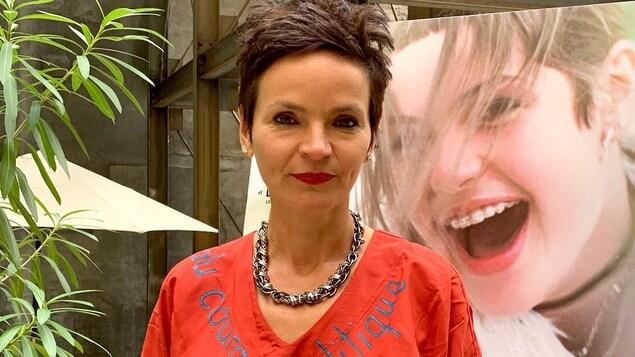 La cinéaste Anaïs Barbeau-Lavalette devant une affiche de son film, La déesse des mouches à feu