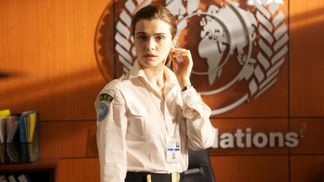 Une femme (Rachel Weisz) en tenue de policière, devant un mur portant le logo de l'O.N.U.
