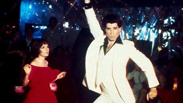 Un homme en costume blanc danse à côté d'une fille en robe rouge.