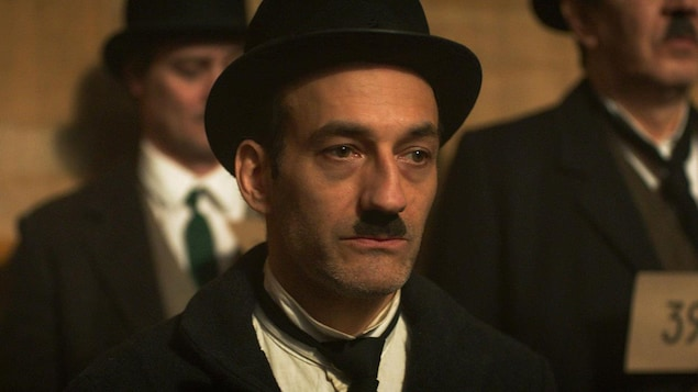 Un homme (Martin Dubreuil) déguisé en Charlie Chaplin, l'air triste.