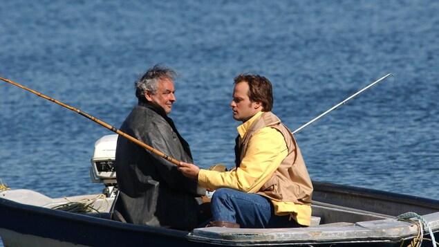 Deux hommes pêchent dans une chaloupe.