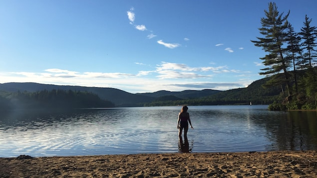 Une femme se baigne dans un lac entouré de nature et d'une plage de sable.