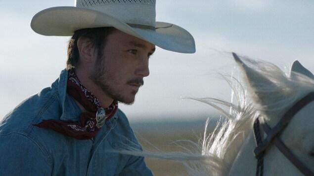 Un homme portant un chapeau de cowboy, à cheval.