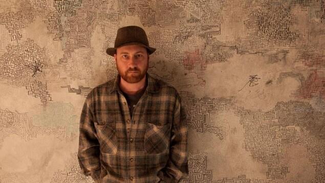Un homme portant un chapeau adossé à un mur.