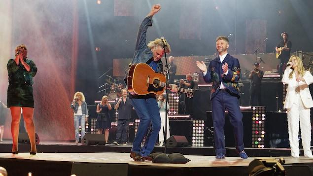 Sur scène, Richard Séguin est avec sa guitare et lève le poing vers le ciel.