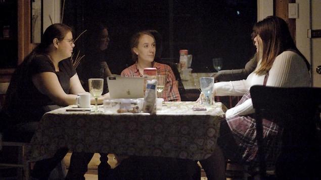 Trois femmes assises autour d'une table.
