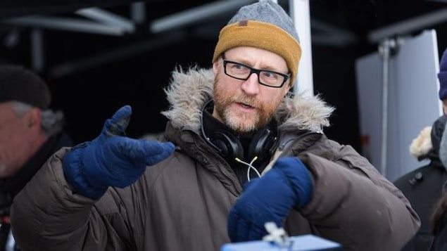 Un cinéaste (Benoît Pilon) portant un manteau d'hiver, une tuque et des gants donne des directions à son équipe.