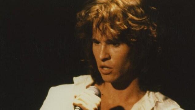 Un homme (Val Kilmer) en chemise blanche, sur fond noir, avec un micro dans les mains.