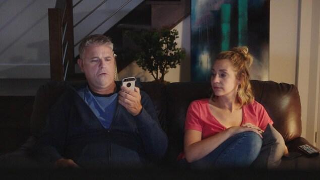 Un couple regarde la télé sur un canapé, il tient son téléphone devant lui et elle essaie de voir l'écran.