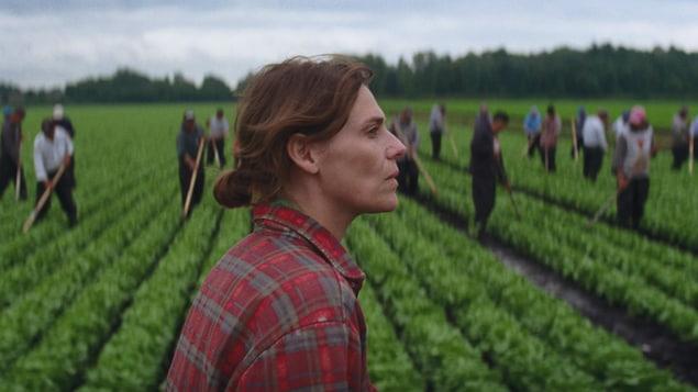 Une femme (Hélène Florent) devant un champ où travaillent des saisonniers mexicains.