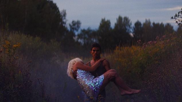 Dans un champ, un jeune homme porte une jeune femme vêtue d'une robe à paillettes dans ses bras.