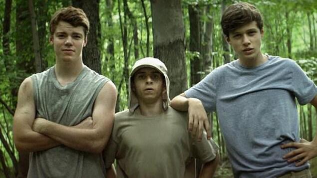 Trois jeunes garçons, de face, en forêt