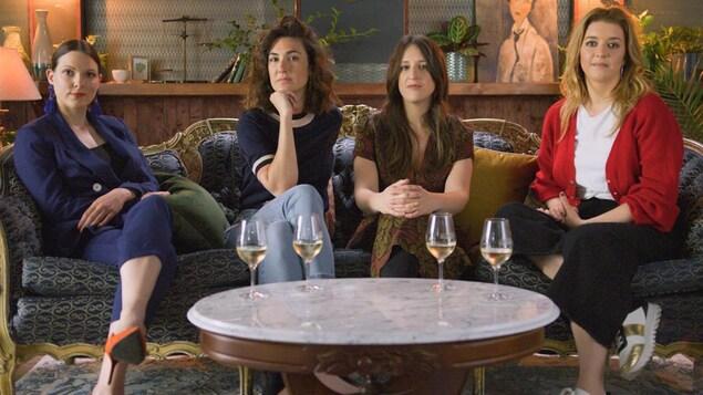 Les 4 filles sont assises sur un élégant canapé. Des verres de vin blanc sont posés sur une table basse devant elles.