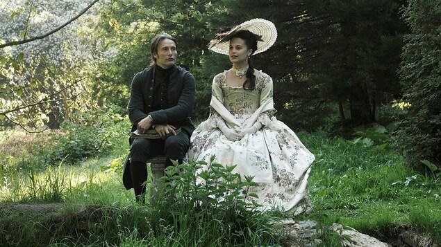 Un homme et une femme en costumes d'époque, assis dans les bois