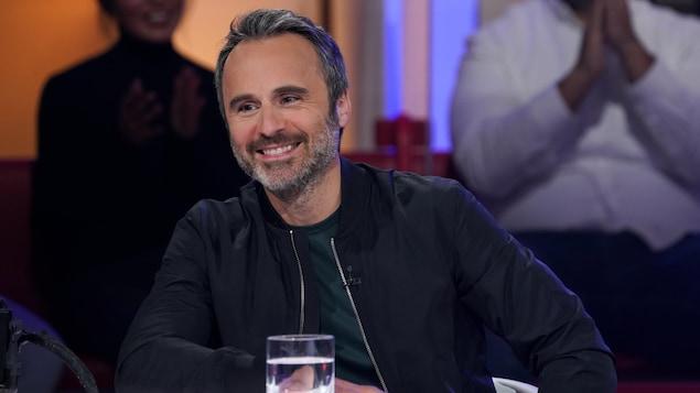 Un homme qui sourit. Il porte un chandail vert et un blouson noir.