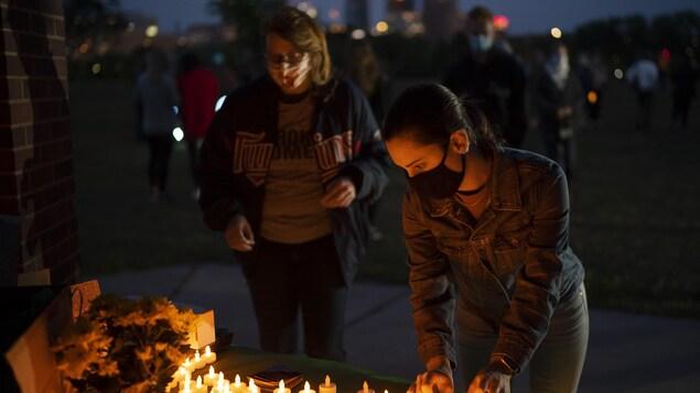 Des gens placent des bougies électriques sur une table avant le service commémoratif pour Ruth Bader Ginsburg.