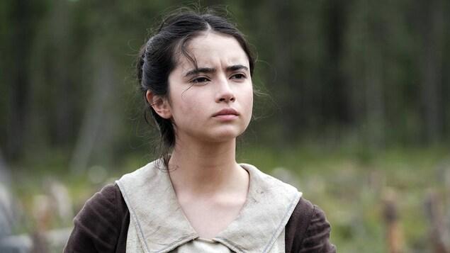 Une jeune femme (Sara Montpetit) en tenue d'époque regarde au loin