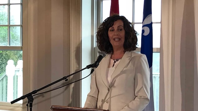 Marie France Trudel devant les drapeaux québécois et canadiens, lors d'un discours.