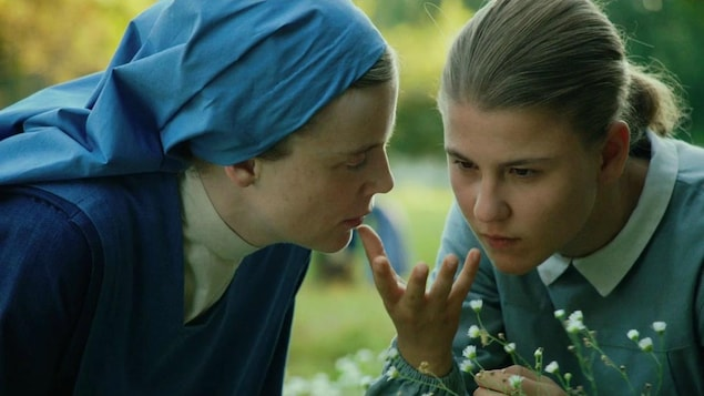 Une femme portant une tenue de religieuse (Isabelle Carré) à côté d'une jeune fille en tenue de pensionnaire, dans un pré.
