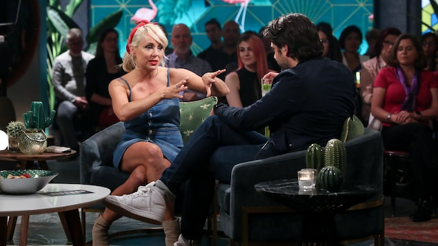 Assise dans un fauteuil, elle discute avec Jean-Philippe Wauthier.