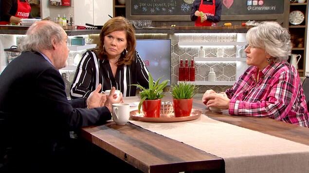 Les trois sont assis à une table et discute. Marina regarde Michel Landry.