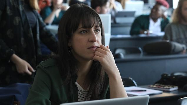 Elle est dans une salle de classe. Elle est attentive.