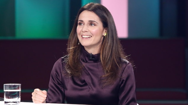 Mélissa Désormeaux-Poulin est à la table des invités. Elle porte une robe de couleur sombre.